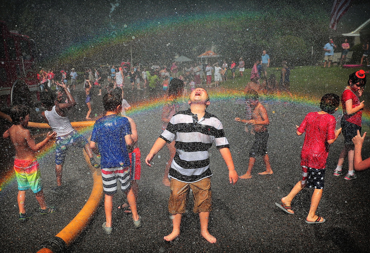 <strong>A rainbow illuminates a crowd of kids as they dance in the spray of the fire hose after the 70th annual Independence Day Parade in the High Point Terrace neighborhood on July 4, 2019. The patriotic gathering was one of several Fourth of July parades throughout Memphis Thursday.</strong> (Jim Weber/Daily Memphian)