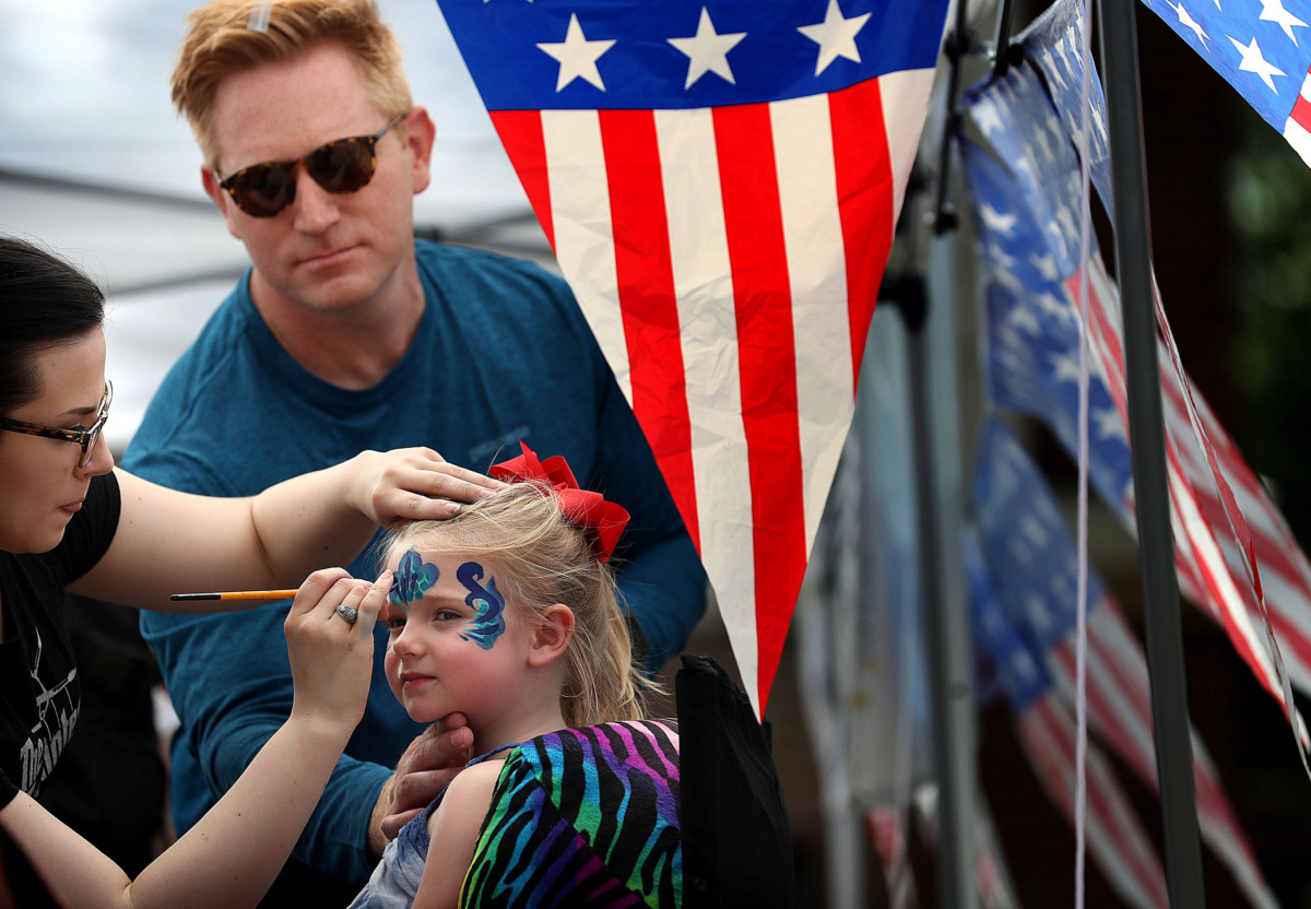 <strong>Todd Sparks helps face painter Michelle Chambers keep his daughter Marjorie, 3, still as she gets adorned after the annual Fourth of July parade in the Cooper-Young neighborhood on July 4, 2019.</strong> (Jim Weber/Daily Memphian)
