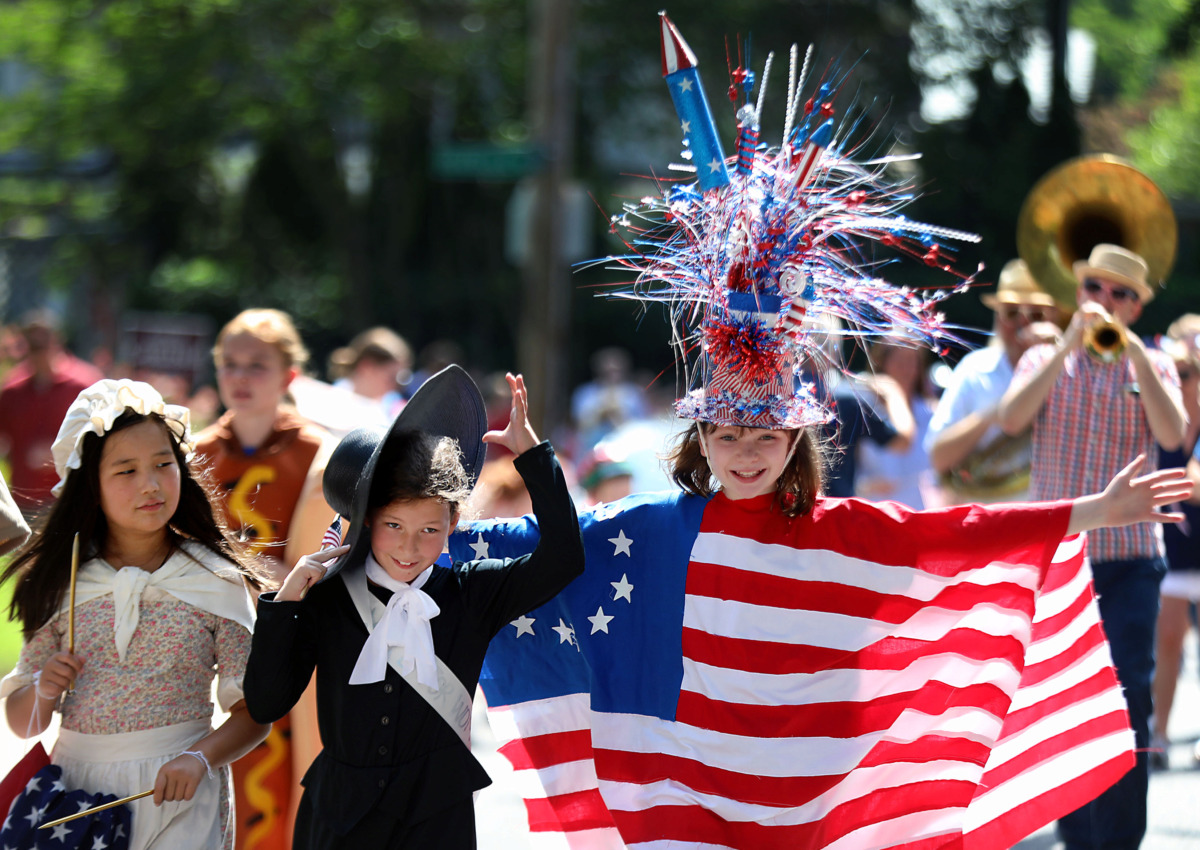 <strong>Dressed as Betsy Ross, Susan B. Anthony, and the original American flag respectively, Ellie Palmer, Virginia Smart and Lilly Loggin lead the Central Gardens neighborhood's Fourth of July parade Thursday, July 4, 2019.</strong> (Patrick Lantrip/Daily Memphian)
