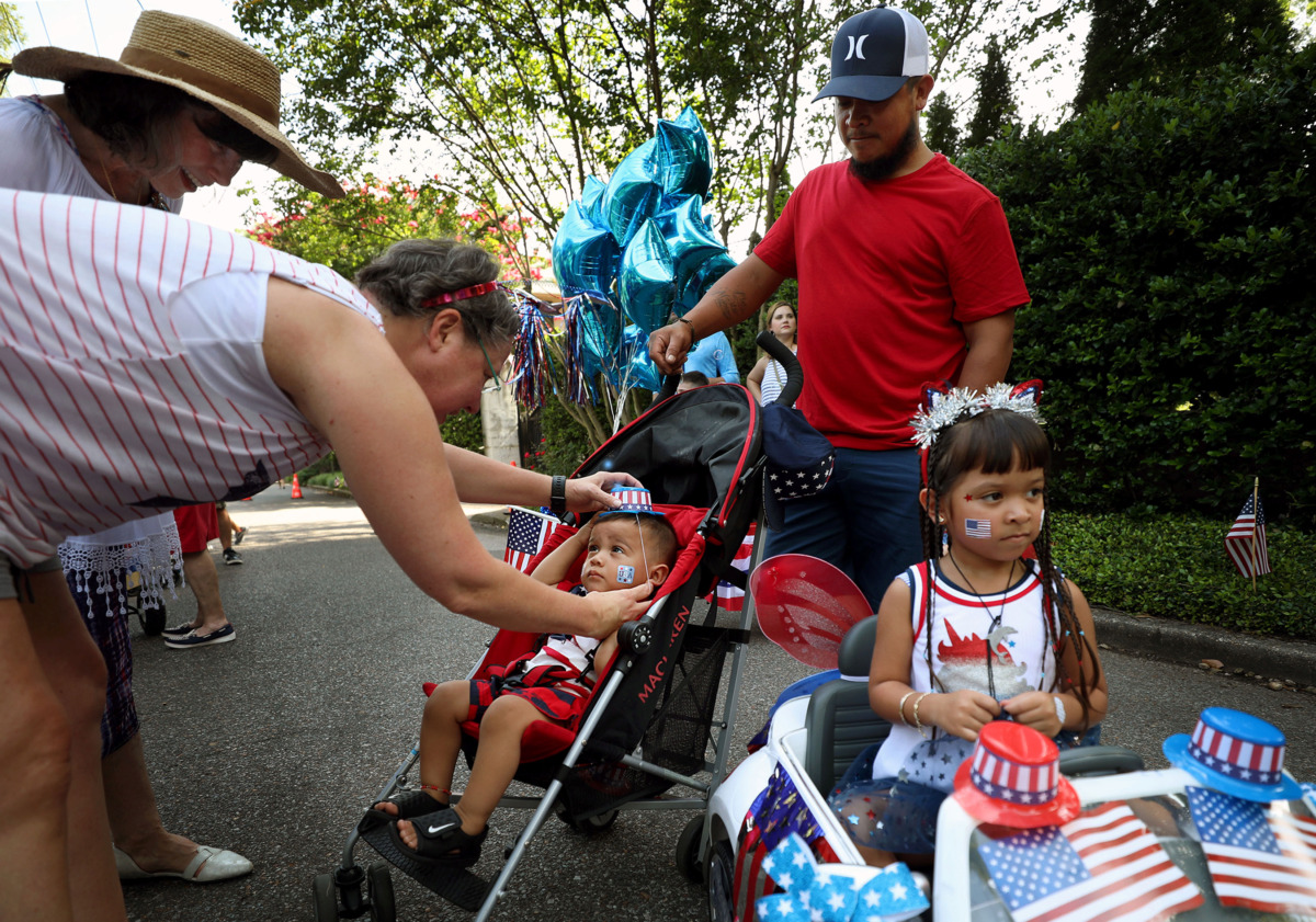 <strong>Shantih Smythe helps young Jayden Palacios get his hat on just before the beginning of Central Gardens' Independence Day parade on Thursday. July 4, 2019.</strong> (Patrick Lantrip/Daily Memphian)