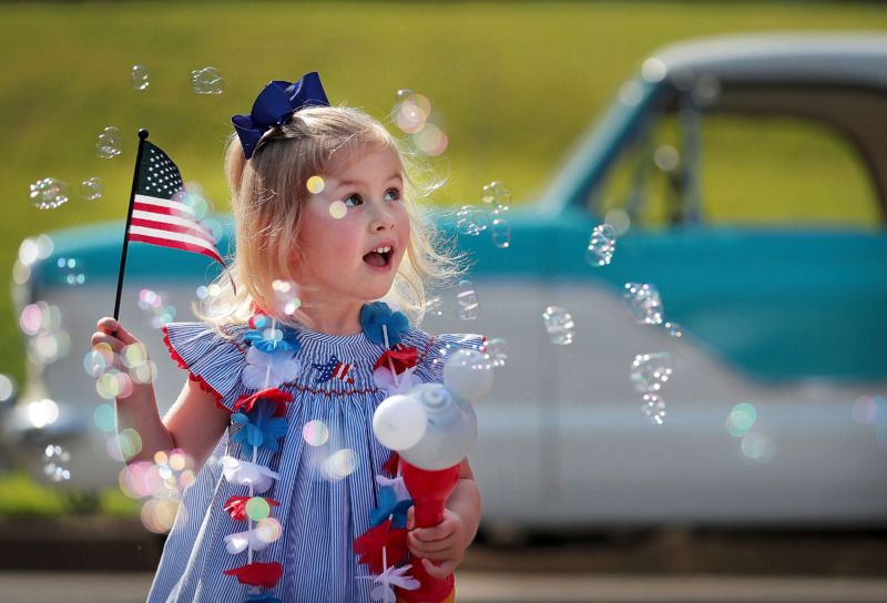 <strong>Four-year-old Lily Priestley makes her own cloud of bubbles before the start of the 70th annual Independence Day Parade in the High Point Terrace neighborhood on July 4, 2019.</strong> (Jim Weber/Daily Memphian)