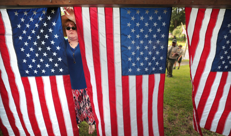 <strong>Lisa St. Gelais (left) hangs flags as a backdrop during the 70th annual Independence Day Parade in the High Point Terrace neighborhood on July 4, 2019.</strong> (Jim Weber/Daily Memphian)