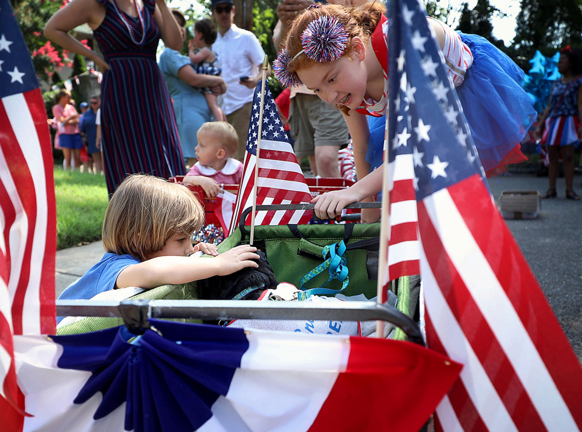 <strong>Ginger the dog soaks up the attention from Wake Gordon as Izzie Cochran looks on Thursday, July 4, 2019.</strong> (Patrick Lantrip/Daily Memphian)