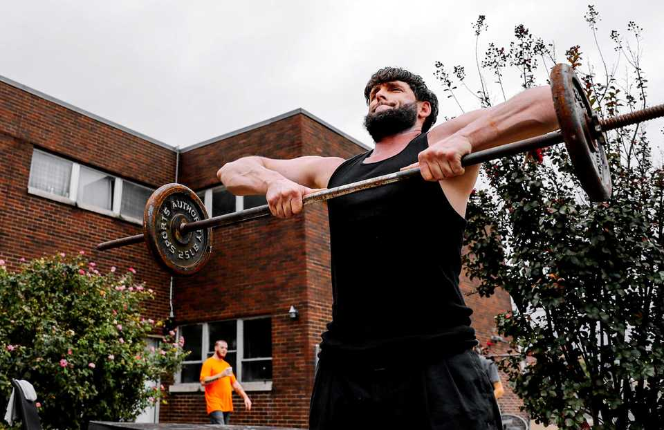 <strong>A guest at Memphis Union Mission goes through his regular workout routine in a side yard outside the mission.</strong> (Houston Cofield/Daily Memphian)