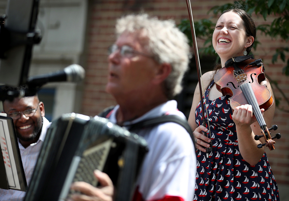 """<strong>Myra Patterson (right) and Joseph Miller (left) from the Museworthies react as fellow band member Jim Bement does a riff on the song """"Grand Old Flag"""" after the annual Fourth of July parade in the Cooper Young neighborhood on July 4, 2019.</strong> (Jim Weber/Daily Memphian)"""