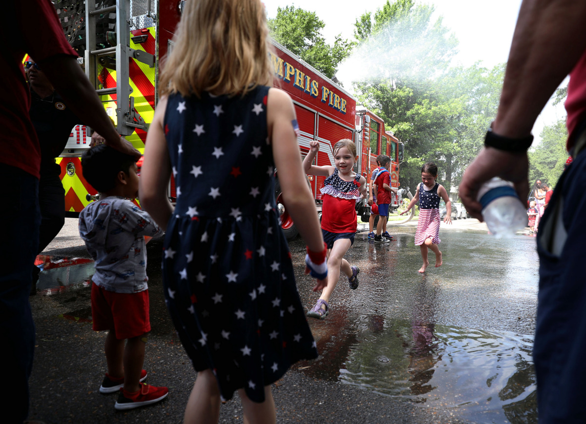 <strong>Isabella Getschman leaps over a puddle at the corner of Willett Street and Carr Avenue after splashing around underneath the fire engine-turned-splashpad Thursday, July 4, 2019.</strong> (Patrick Lantrip/Daily Memphian)