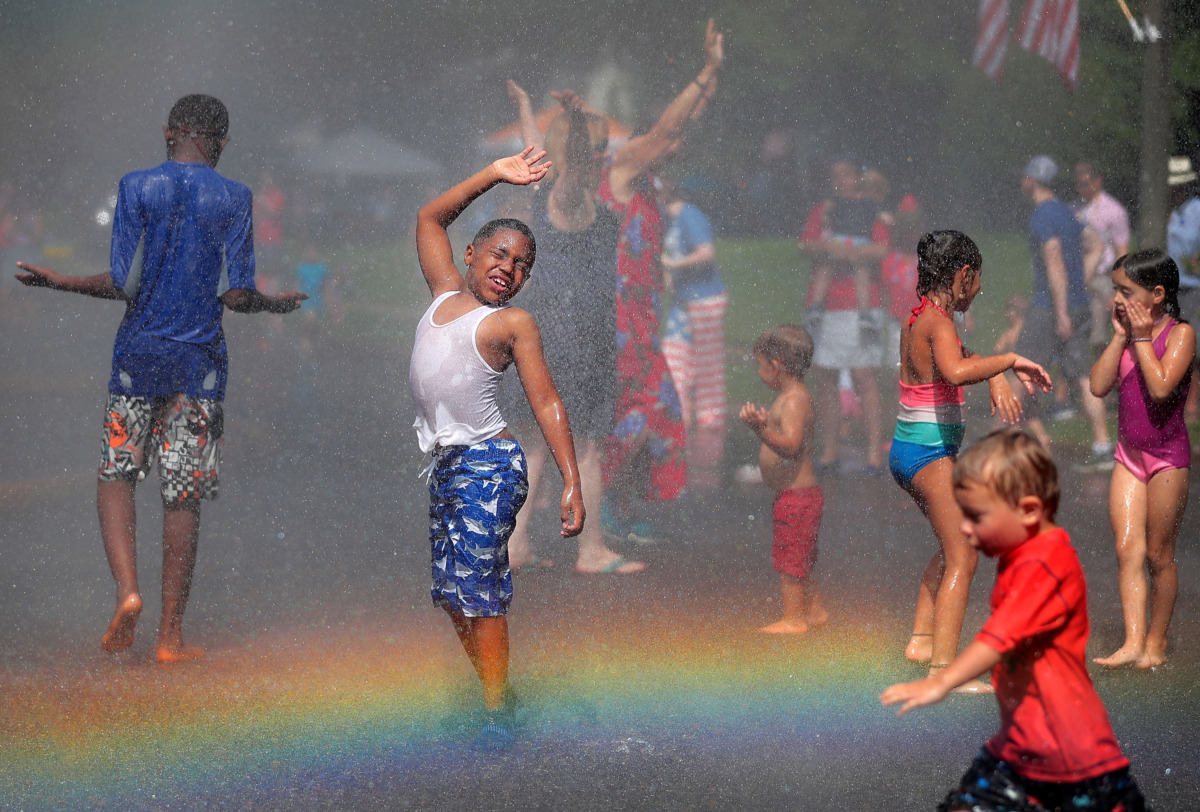 <strong>A rainbow illuminates Jacai Foster (center) and a crowd of kids as they dance in the spray of the fire hose after the 70th annual Independence Day Parade in the High Point Terrace neighborhood on July 4, 2019. Once again East Memphis residents gathered for a patriotic morning of star-spangled bikes, waving neighbors and a dousing by the Memphis Fire Department.</strong> (Jim Weber/Daily Memphian)