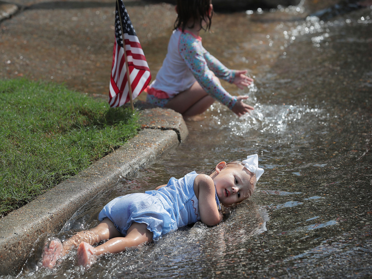 <strong>Two-year-old Anne Tipton Rogers relaxes in the cool runoff from the fire hose as kids play in the spray after the 70th annual Independence Day Parade in the High Point Terrace neighborhood on July 4, 2019. Once again East Memphis residents gathered for a patriotic morning of star-spangled bikes, waving neighbors and a dousing by the Memphis Fire Department.</strong> (Jim Weber/Daily Memphian)