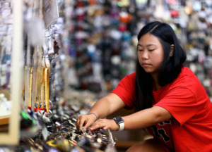 <strong>Lauren Kim stocks a sunglasses display at Jun Lee Trading Co., the shop her parents have operated at 3397 Summer Ave. for 32 years.</strong>&nbsp;(Patrick Lantrip/Daily Memphian)