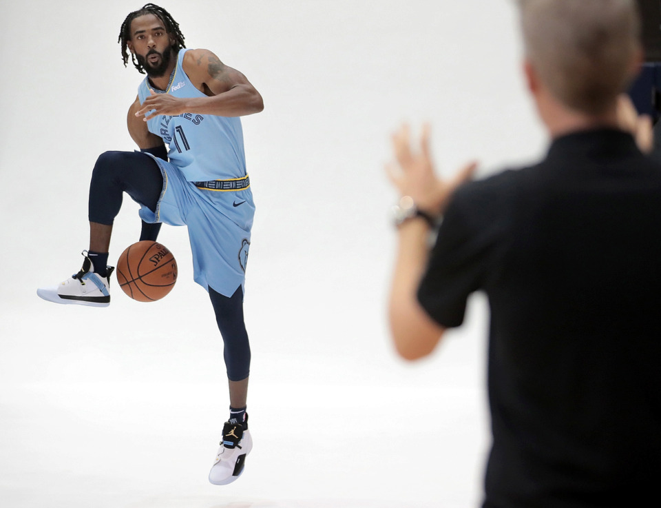 <strong>Mike Conley adds a little action to his portrait session during the 2018 Grizzlies media day at the FedExForum. Grizzlies owner Robert Pera says team will retire the No. 11 jersey of the traded point guard.</strong> (Jim Weber/Daily Memphian)