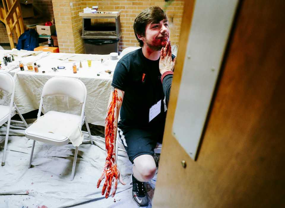 "<strong>Donna Dobro applies fake blood and other makeup on Dylan Price, 21, before an airport disaster drill at Memphis International Airport on Monday, Oct. 15.&nbsp;<span style=""color: black;"">The Federal Aviation Administration requires a full-scale disaster exercise every three years. After a 2016 drill, Memphis airport officials decided to have it every two years to sharpen emergency-response procedures.</span></strong>&nbsp;(Houston Cofield/Daily Memphian)"