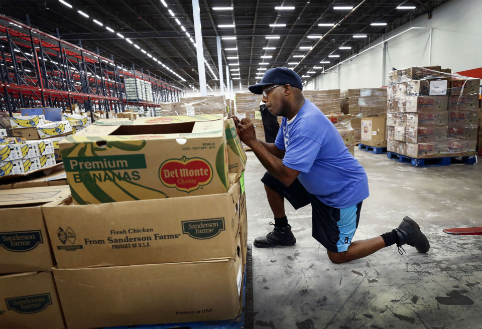 <strong>Mid-South Food Bank warehouse employee Michael Taylor weighs donated foods as workers deliver product to its new 167,000-square-foot warehouse and office space at 3865 S. Perkins Road on Monday, July 8, 2019. The new facility will double the organization's capacity for getting food to those in need.</strong> (Mark Weber/Daily Memphian)