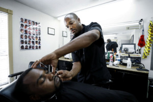 <strong>Barber Carnell Vann Jr. touches up customer Jessie Marshall Jr.&rsquo;s edges while giving him a haircut Tuesday, July 9, 2019. Vann recently received a $20,000 Inner City Economic Development loan to open his own barbershop in the Frayser area.</strong> (Mark Weber/Daily Memphian).