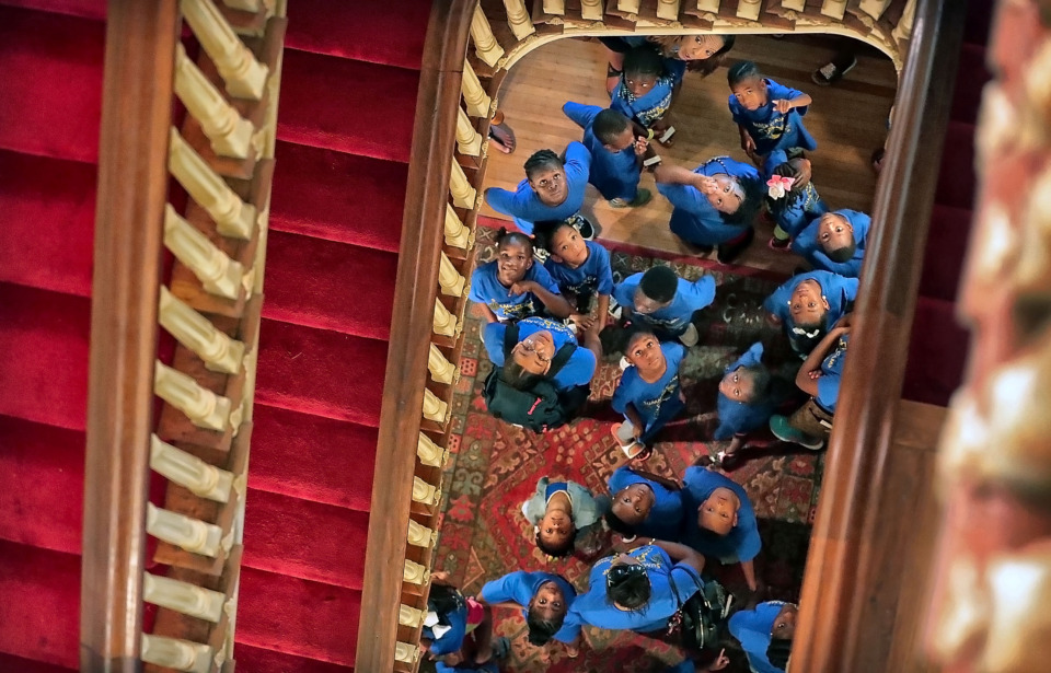 <strong>Gazing up at the moldings and chandeliers of the grand stairway, children participating in Agape's summer program tour the Woodruff-Fontaine House in Victorian Village on Thursday, July 11. A group of some 90 children of all ages visited the storied home while learning about famous African-Americans in the city's history.</strong> (Jim Weber/Daily Memphian)
