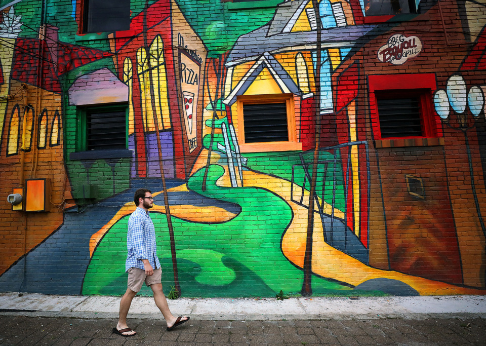 <strong>Parker Holland walks by the colorful Overton Square on the north side of Bari Ristorante on Wednesday, July 10. The revival of Overton Square has made nearby properties the target of acquisition by developers.</strong> (Patrick Lantrip/Daily Memphian)