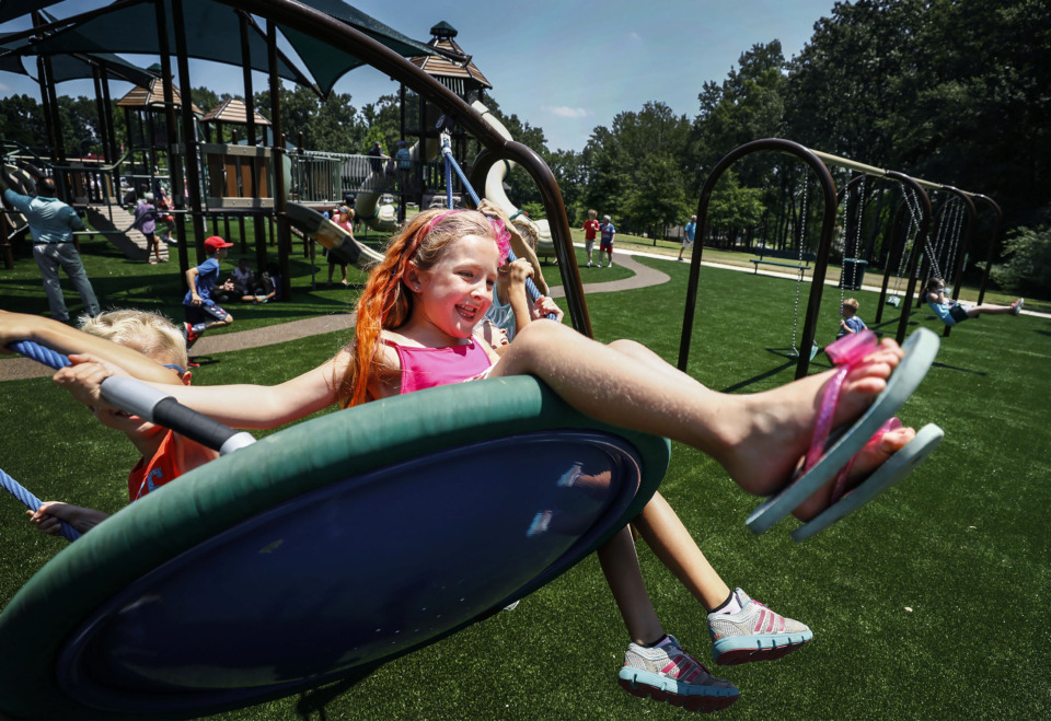 <strong>Brooke Winburn, 6, swings at the newly rebuilt Playground of Dreams in Arlington, during a grand-opening event Friday, July 12, at Hughes-College Hill Park. The old playground was torn down in March after becoming dilapidated and being declared unsafe.&nbsp;</strong>(Mark Weber/Daily Memphian)