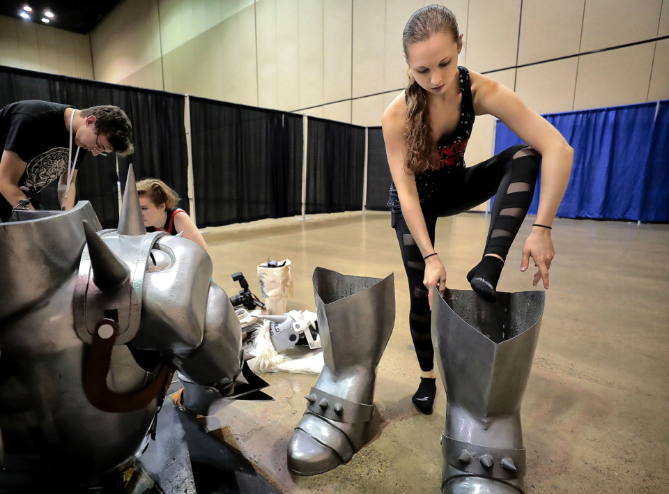 "<strong>Meagan Herbold, 19, climbs into the boots of her 7-foot Alphonse Elric costume. Herbold's father,&nbsp;John Herbold, crafted the likeness of the ""Full Metal Alchemist"" character from fiberglass and carbon fiber.&nbsp;</strong>(Jim Weber/Daily Memphian)"
