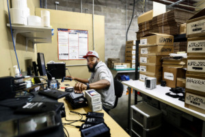 <strong>Alvin Tunstall, warehouse lead at Surge Holdings, works on smartphone inventory at the company&rsquo;s new facility in Bartlett, on Friday, July 12. Surge moved its company headquarters from Las Vegas to the Brother Boulevard corridor in Bartlett.</strong> (Mark Weber/Daily Memphian)