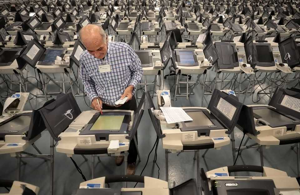 <strong>Volunteer Rick Riedell works on getting the voting machines ready on Oct. 16, 2018, at the Election Commission Operations Center in advance of early voting.</strong> (Jim Weber/Daily Memphian)