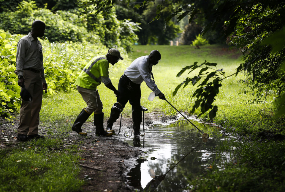 <strong>Vector Control supervisor Fredrick Mack (right) along with Jermaine Hughley (middle) and James Washington (left) search for mosquito larvae in puddles near Central Avenue in Midtown.</strong> (Mark Weber/Daily Memphian)