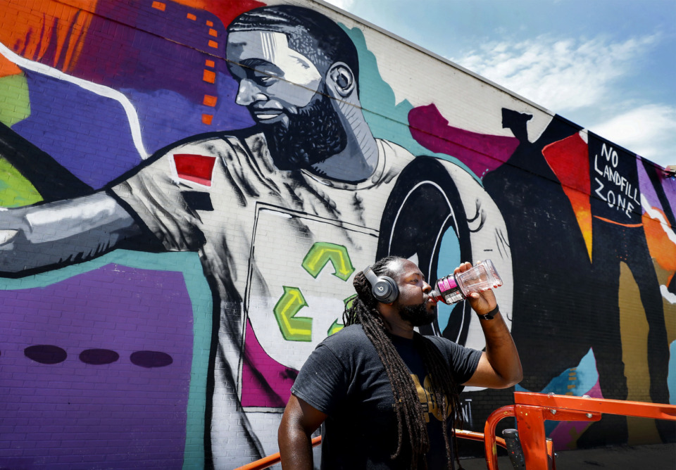 <strong>Local artist Jamond Bullock takes a long swig of a refreshing drink on a hot July day, while completing a mural in Frayser, his home neighborhood. The mural is part of an initiative with the UrbanArt Commission in Memphis.</strong> (Mark Weber/Daily Memphian).