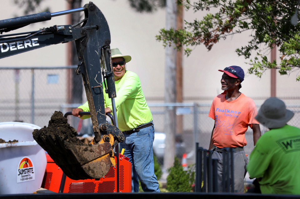 <strong>Daniel Marquez (left) laughs with Sylvester Turnage and Leotto Smith while building a new fountain on Smith &amp; Nephew&rsquo;s Brooks Road campus.</strong> (Patrick Lantrip/Daily Memphian)