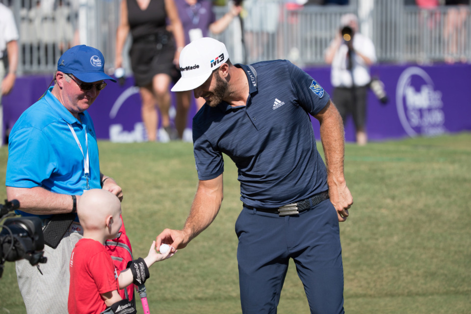 <strong>Dustin Johnson took home the FedEx St. Jude Classic winner's check in 2012 and again in 2018. Each time, he spent some pre-tournament time with St. Jude patients. </strong>&nbsp;(Photo courtesy of ALSAC/St. Jude Children's Research Hospital)