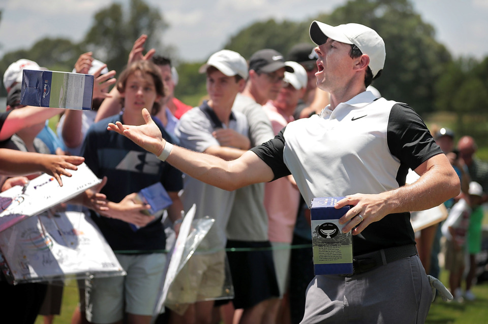 <strong>Rory McIlroy passes out bobbleheads disgorged from a robot on the 9th green during a day of practice rounds at the WGC - FedEx St. Jude Invitational at TPC Southwind on July 24, 2019.</strong> (Jim Weber/Daily Memphian)