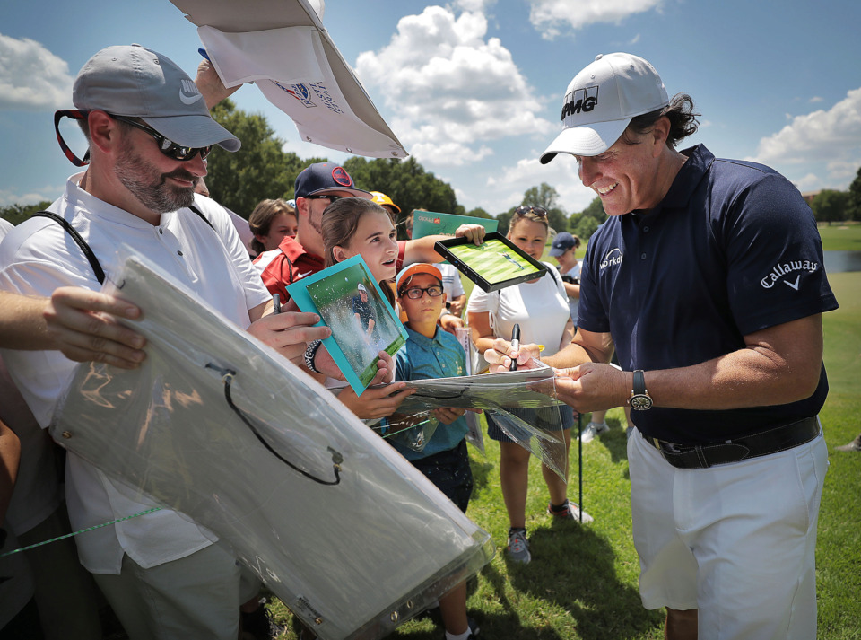 <strong>Phil Mickelson (right) signs autographs on the 9th green during a day of practice rounds at the WGC - FedEx St. Jude Invitational at TPC Southwind on Wednesday, July 24, 2019.</strong> (Jim Weber/Daily Memphian)