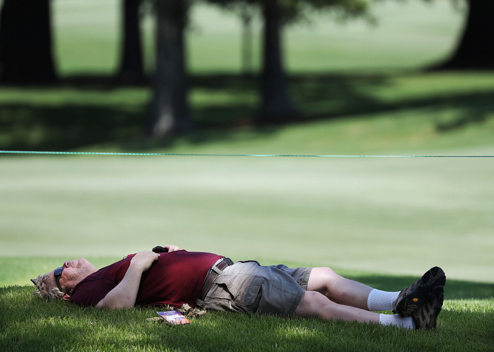 <strong>Scott Saunders of Madison, Ala., takes a nap while waiting for golfers to pass by during a day of practice rounds at the WGC - FedEx St. Jude Invitational at TPC Southwind on Wednesday, July 24, 2019.</strong> (Jim Weber/Daily Memphian)