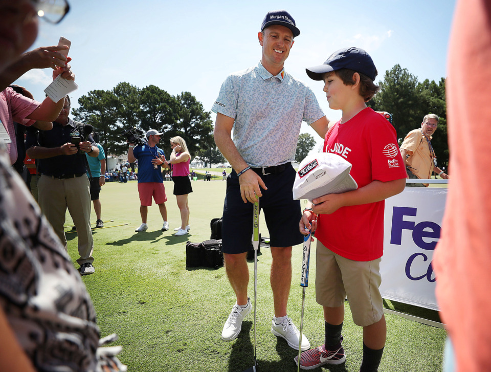 <strong>Justin Rose gets a token from fan Dakota Cunningham while signing autographs on the practice green during a day of practice rounds at the WGC - FedEx St. Jude Invitational at TPC Southwind on Wednesday, July 24, 2019.</strong> (Jim Weber/Daily Memphian)