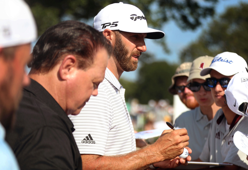 """<strong>Golfer Dustin Johnson (back) and wrestler Jerry """"the King"""" Lawler sign autographs with fans after the first round of the WGC-FedEx St. Jude Invitational at TPC Southwind, Thursday, July 25, 2019.</strong> (Patrick Lantrip/Daily Memphian)"""