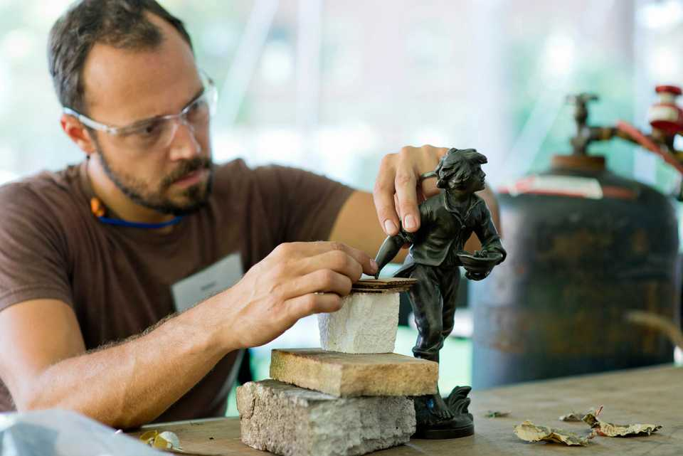 <span><strong>Volunteer metalsmith Adam Hawk re-attaches the broken arm of a metal figurine at the National Ornamental Metal Museum.</strong> (National Ornamental Metal Museum)</span>