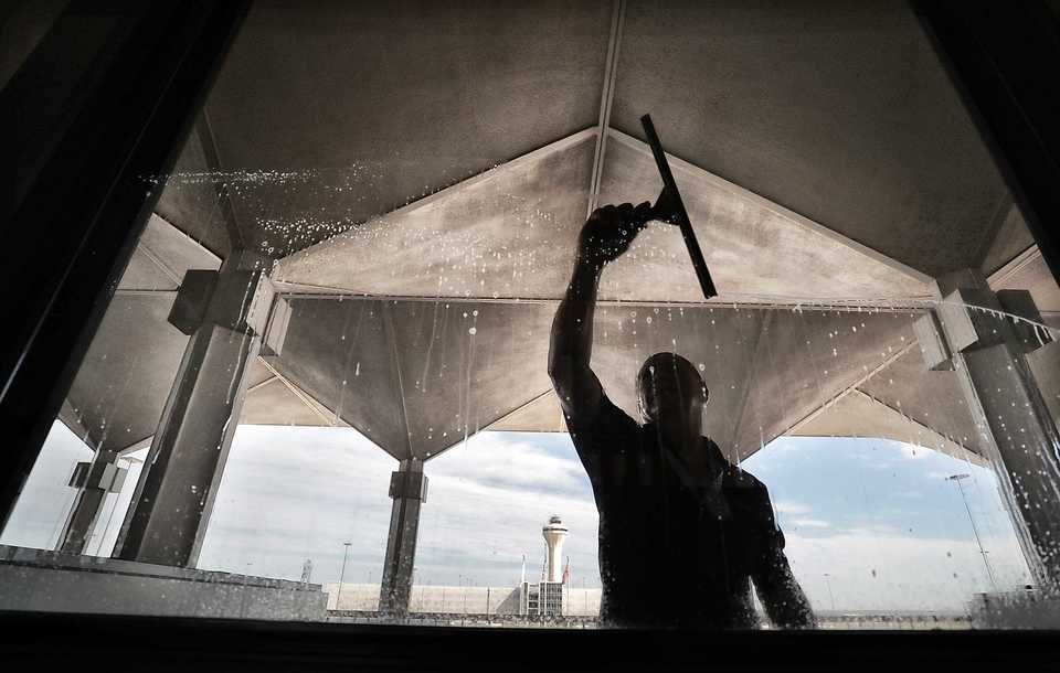 With the control tower in the background, Louis Arias cleans the windows on the B terminal at Memphis International Airport on Sept. 5, 2018. The airport isn't planning to slow down after the three-year, $245 million B concourse modernization is complete. Airport officials also are looking to improve parking and renovate the B terminal. (Jim Weber/Daily Memphian)
