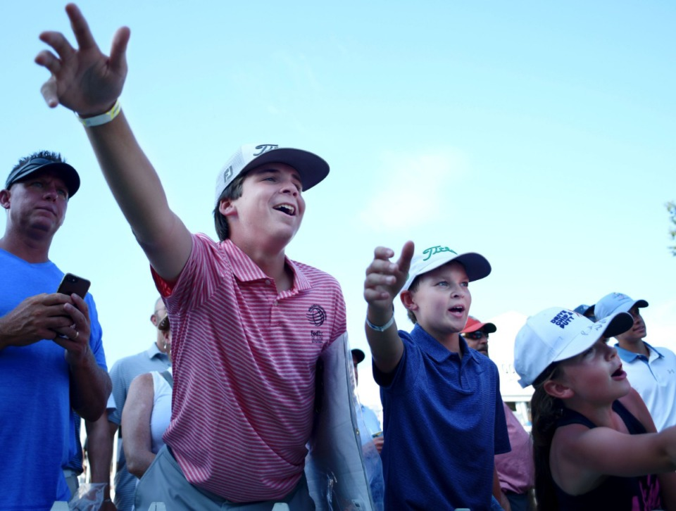 <strong>Webie Kramer (from left), 14, Aidan Taylor, 12, and Lily Chartrand, 7, shout for Dustin Johnson as he walks off the 18th green during the 2019 WGC-FedEx St. Jude Invitational on July 26, 2019, at TPC Southwind.</strong> (Houston Cofield Special To The Daily Memphian)