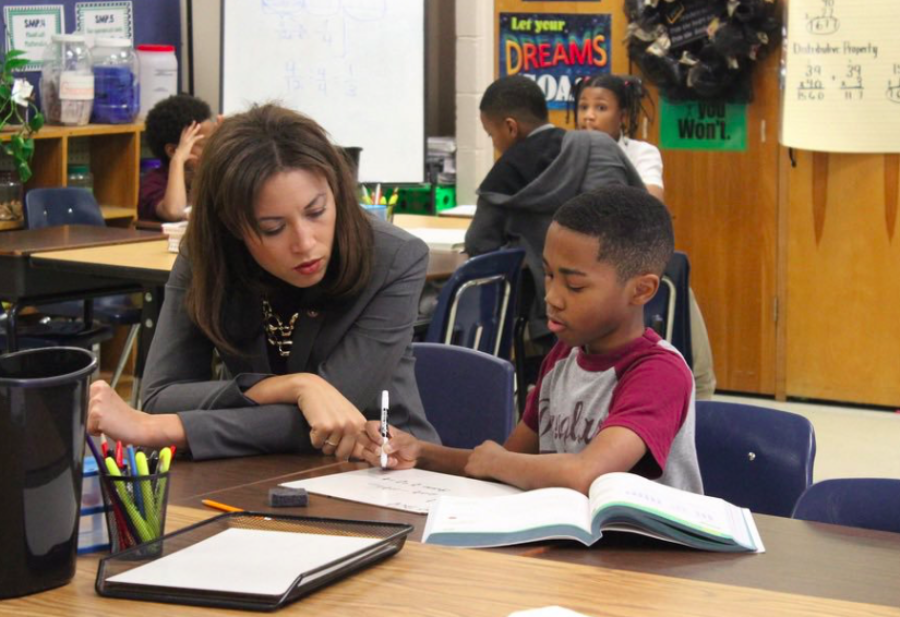 <span><strong>Penny Schwinn looks at classwork with a student in Memphis in February, soon after becoming Tennessee's education commissioner. Schwinn has ordered a one-year delay in the plan to begin giving Tennessee schools A-F ratings based on quality.</strong> (Photo courtesy of Tennessee Department of Education)</span>