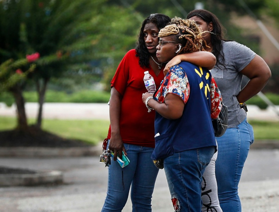 <strong>Walmart employees and family members sit in a nearby parking lot after two people were killed and the suspect and police officer were injured during an early-morning shooting at the store in Southaven, Mississippi, Tuesday, July 30, 2019.</strong><span>&nbsp;(Mark Weber/Daily Memphian)</span>