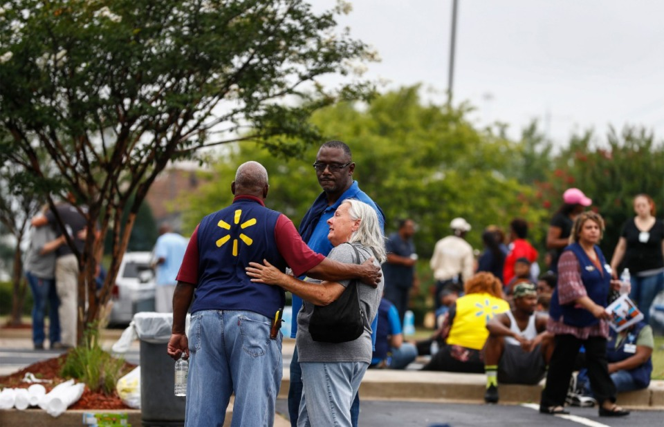<strong>Walmart employees comfort each other in a nearby parking lot after two people were killed and the suspect and a police officer were injured during an early morning shooting at the store in Southaven, Miss., on Tuesday, July 30.</strong> (Mark Weber/Daily Memphian)
