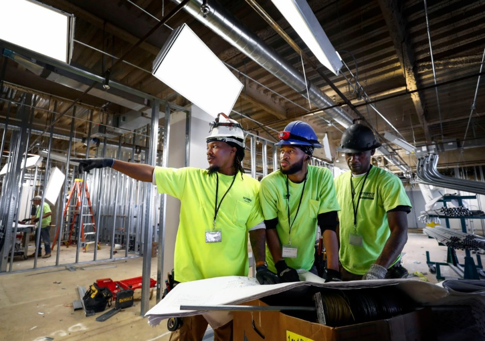 <strong>Electricians Nick Collins (from left), Javon Byars and Dary Hayes look over blueprints while wiring the third floor of the Criminal Justice Center on July 9, 2019. Shelby County is in the midst of remodeling the 1980s-era CJC building at 201 Poplar, which houses criminal courts and the DA's, public defender's and clerks' offices.</strong> (Mark Weber/Daily Memphian)