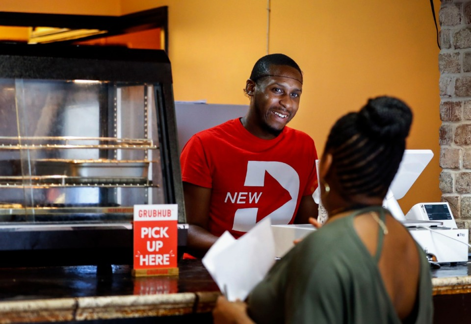 <strong>Caribbean Flayvahz owner Louis Faulkner takes customers' orders at the restaurant he and his wife, Carla, own in Hickory Hill. &ldquo;This is where God led us,&rdquo; Faulkner said of the location.</strong> (Mark Weber/Daily Memphian)