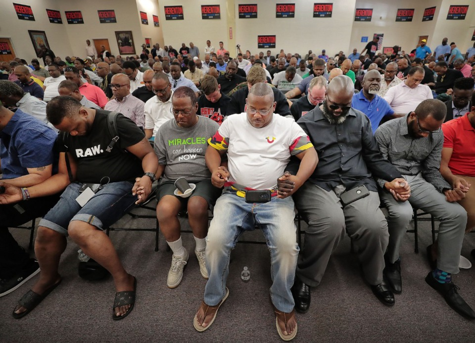 <strong>Willie Herenton supporters clasp hands for prayer during a Donuts With Doc rally at the mayoral candidate's campaign headquarters in South Memphis on Aug. 3, 2019.</strong> (Jim Weber/Daily Memphian)