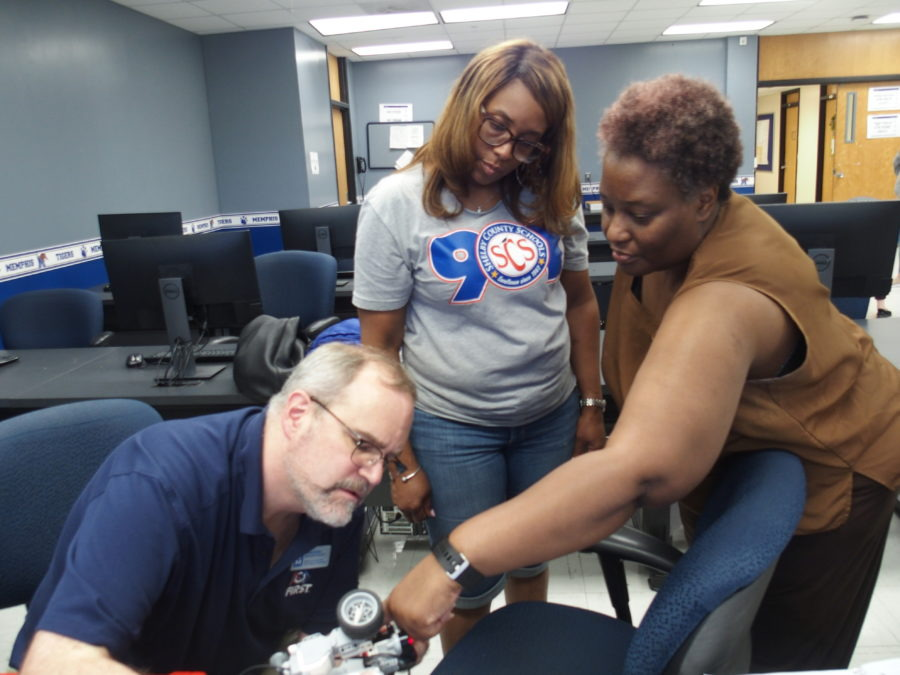 <strong>University of Memphis engineering professor Daniel Kohn (left) helps local science teachers Iris Myers (center) and Sonya Boyce program a robot during a robotics teacher training on campus.</strong> (Kathryn Palmer/Chalkbeat)