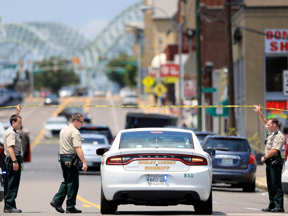 <strong>Several Sheriff's Office deputies let a field commander through the police tape that was blocking off Poplar in the wake of an officer-involved shooting in Downtown Memphis Monday, Aug. 5.</strong> (Patrick Lantrip/Daily Memphian)