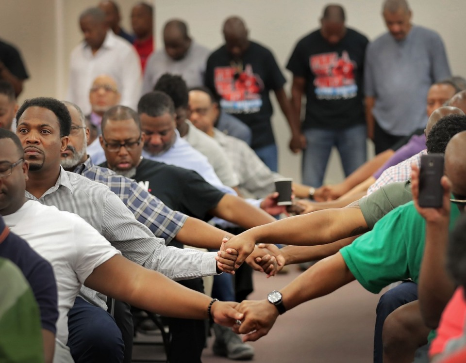<strong>Herenton supporters clasp hands for prayer during a Donuts With Doc rally at mayoral candidate Willie Herenton's campaign headquarters in South Memphis on Saturday, Aug. 3.</strong> (Jim Weber/Daily Memphian)