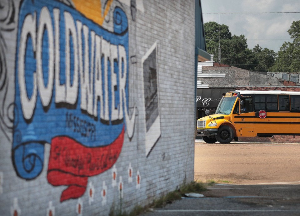 <strong>A Tate County school bus motors by the corner of downtown Coldwater, Mississippi, where the original Fred's store now sits closed and vacant. It's emblematic of hundreds of stores, many of them in small rural communities, that are going out of business due to the Memphis-based discount store chain's struggles.</strong> (Jim Weber/Daily Memphian)