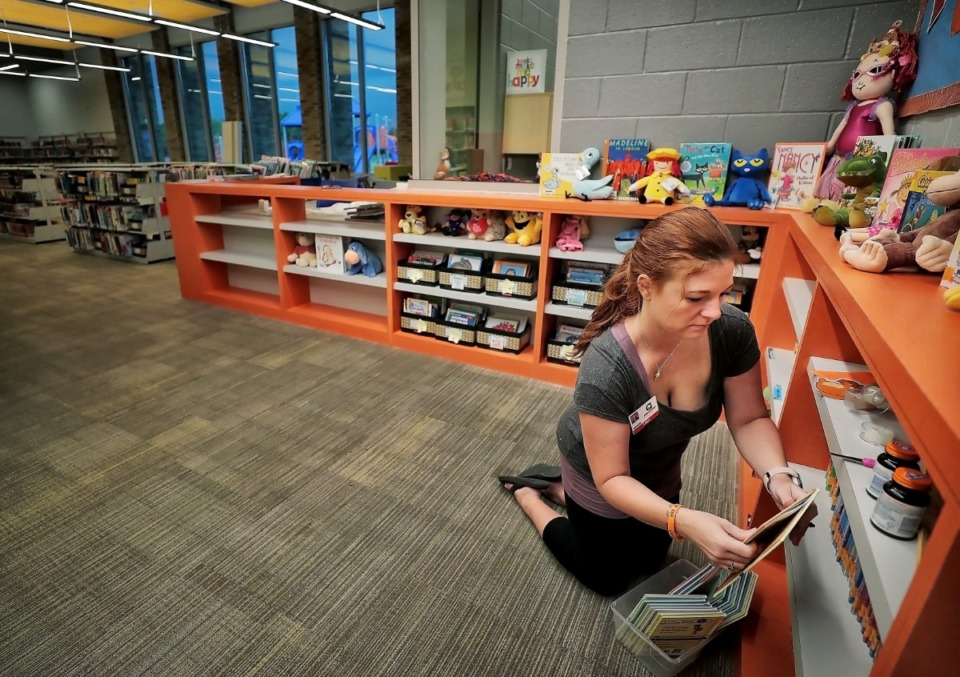 <strong>Librarian Jennifer Mock organizes displays at the entrance to her new library stocked with all new books on Aug. 8, 2019&nbsp;as teachers, administrators and construction crews put the finishing touches on Germantown's new Forest Hill Elementary.&nbsp;</strong>(Jim Weber/Daily Memphian)