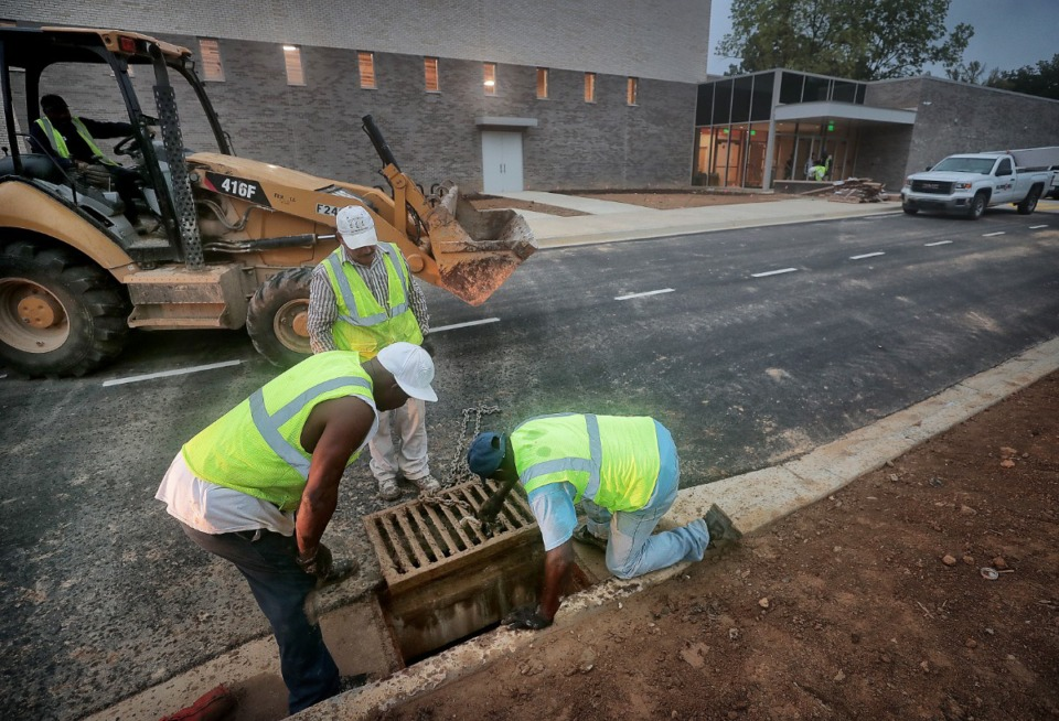 <strong>Workers replace a storm drain in front of&nbsp;Germantown's new Forest Hill Elementary as finishing touches are being put on the school on Aug. 8, 2019.</strong>&nbsp;(Jim Weber/Daily Memphian)