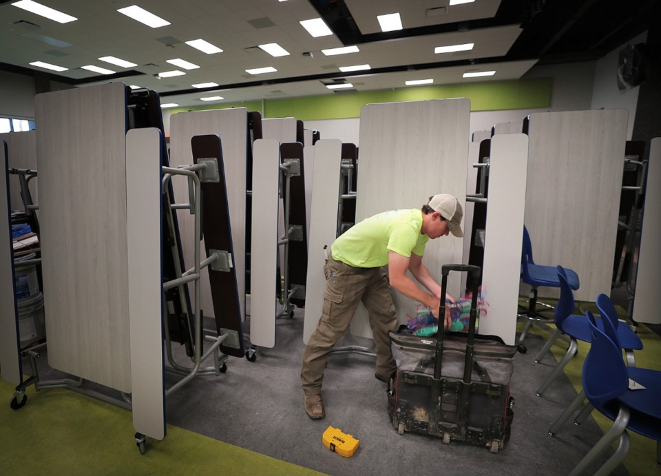 <strong>Brett Ashmore works on wiring in the cafeteria as teachers, administrators and construction crews put the finishing touches on Germantown's new Forest Hill Elementary on Aug. 8, 2019.</strong>&nbsp; (Jim Weber/Daily Memphian)