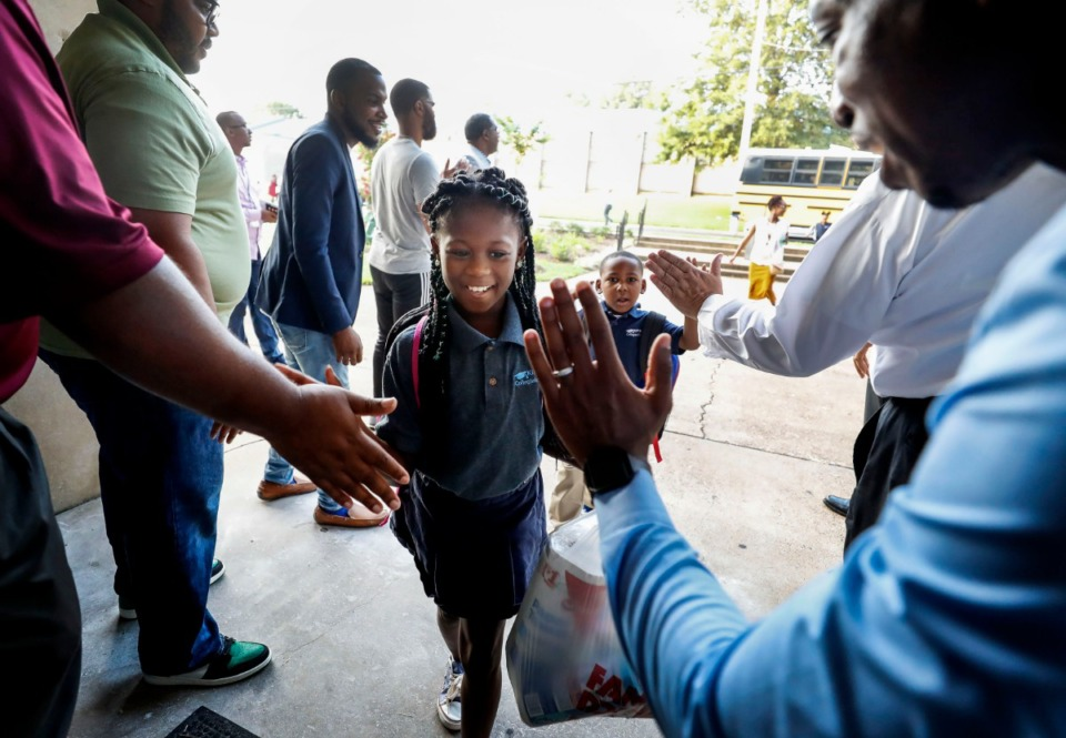 <strong>On the first day of school, third-grader D'Asiah Franklin, 8, receives high-fives while being greeted during the Men's Morning Huddle at KIPP Collegiate Elementary School Monday, Aug. 12.</strong> (Mark Weber/Daily Memphian)