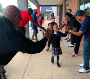 <strong>Community members in the Hickory Hill neighborhood offer cheers and high-fives to welcome students back to Power Center Academy Elementary School.</strong><span>&nbsp;(Photo courtesy of Power Center Academy)</span>